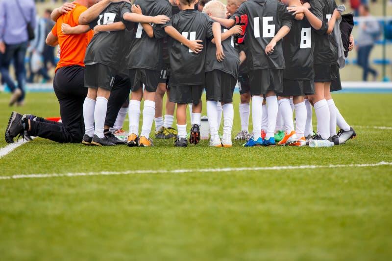 Young Boys im Fußball-Fußball Team With Coach Motivations-Gespräch B stockbild