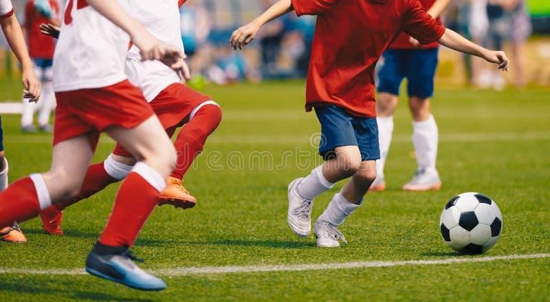 Young Boys nas camisas brancas e vermelhas do jérsei de futebol e nos grampos do futebol que retrocedem a bola de futebol foto de stock