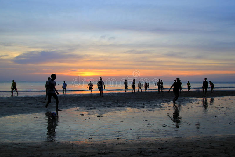 The young boys are playing football on the beach on the background of colorful sunset. royalty free stock photography