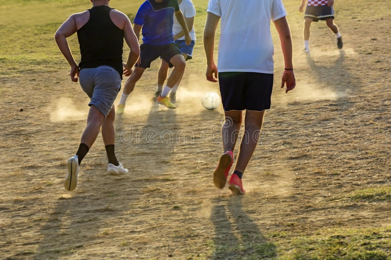 Young boys playing football game. On the sunset stock photos