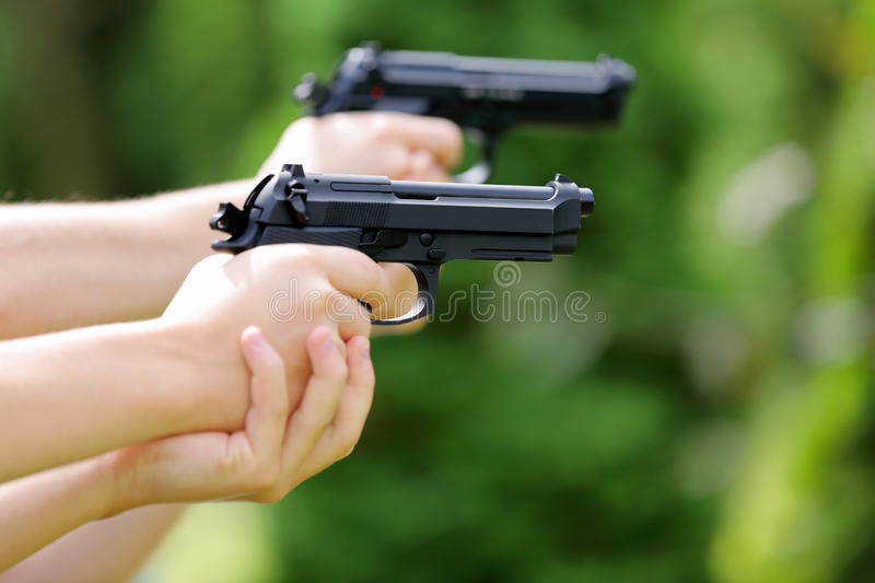 Young boys practice shooting guns on outdoor stock photo