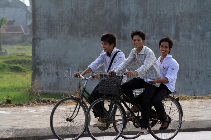 Riding from school. Young boys riding home from school on their bikes, one balancing just above the wheel