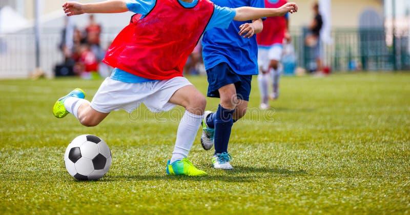 Young Boys som sparkar fotbollbollen på graden för grönt gräs fotbolllek royaltyfri foto