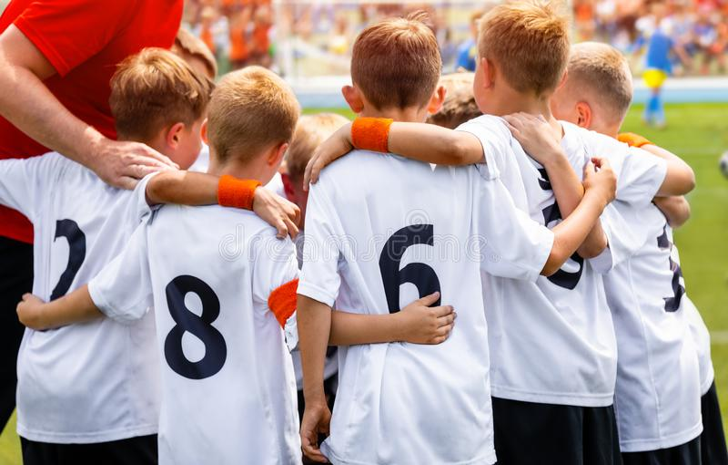 Young Boys in Voetbalteam Groep Kinderen in Voetbalteam De Toespraak van Coach's Pregame van de schoolvoetbal royalty-vrije stock afbeeldingen