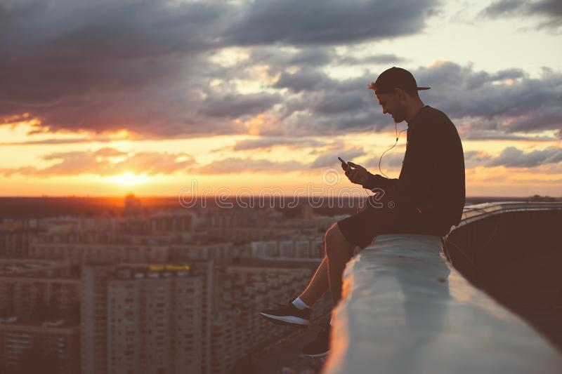 Young brave man sitting on the edge of the roof with smartphone royalty free stock photos