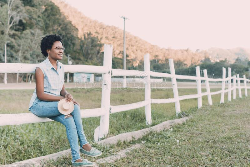 Young brazilian woman looking smiling and looking away. And using glasses. Woman with afro style hair sitting on farm fence royalty free stock photography