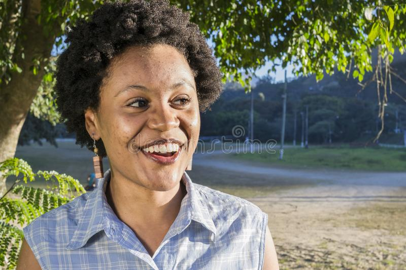 Young brazilian woman with surprised expression. Young African American or Brazilian woman with suprised expression during sunny afternoon. Afro style hair and stock image