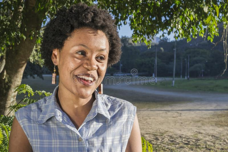 Young brazilian woman with surprised and happiness expression. Young African American or Brazilian woman smiling during sunny afternoon. Afro style hair and stock photo