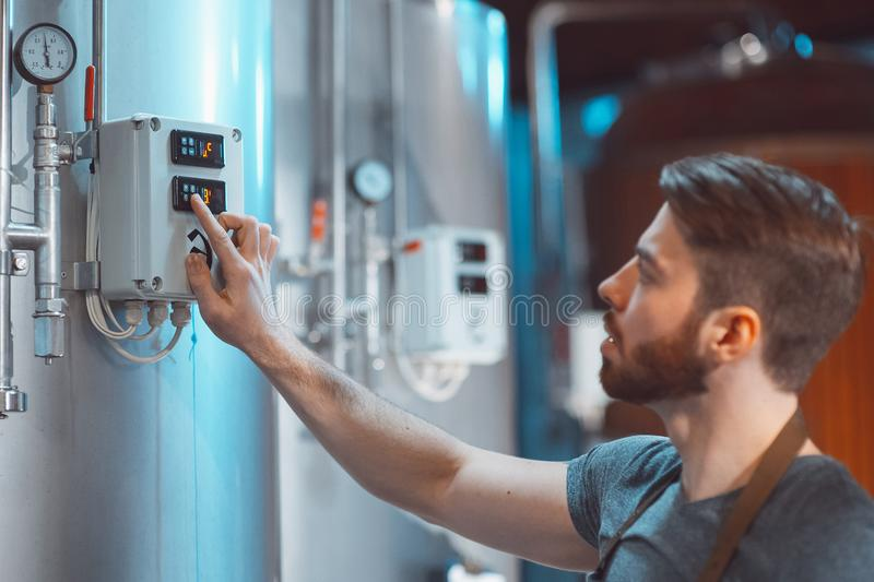 Young Brewer adjusts temperature sensors on beer tanks.  royalty free stock photos