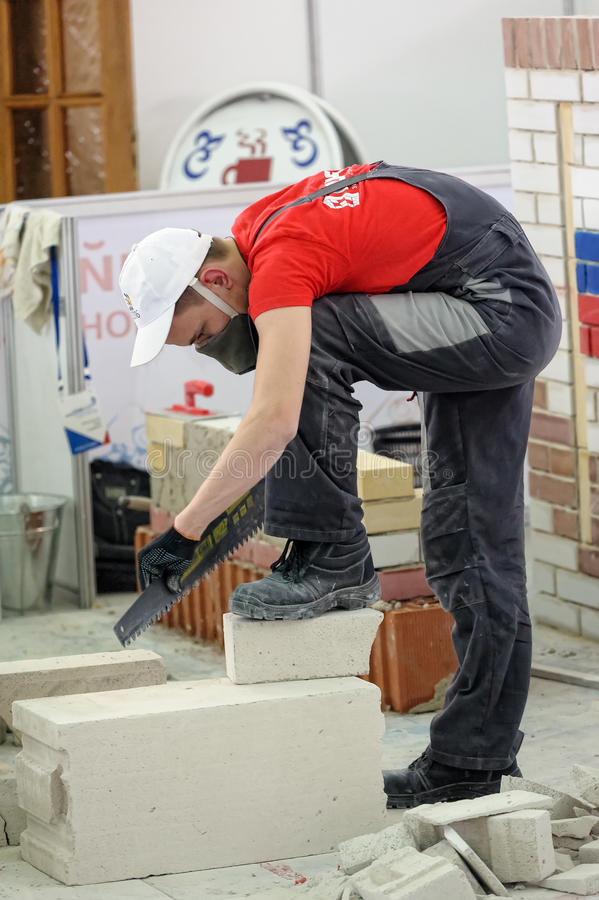 Young bricklayer performs a task of competition. Tyumen, Russia - February 16. 2017: Open championship of professional skill among youth World skills Russia royalty free stock image