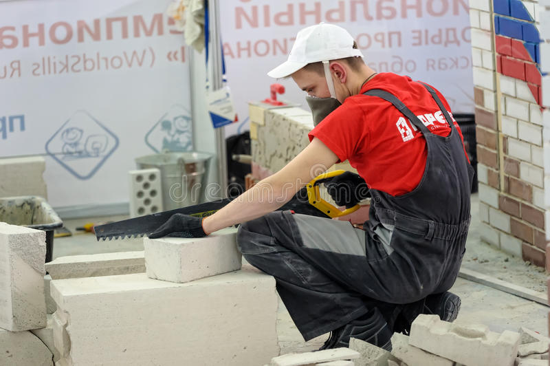 Young bricklayer performs a task of competition. Tyumen, Russia - February 16. 2017: Open championship of professional skill among youth World skills Russia stock photography