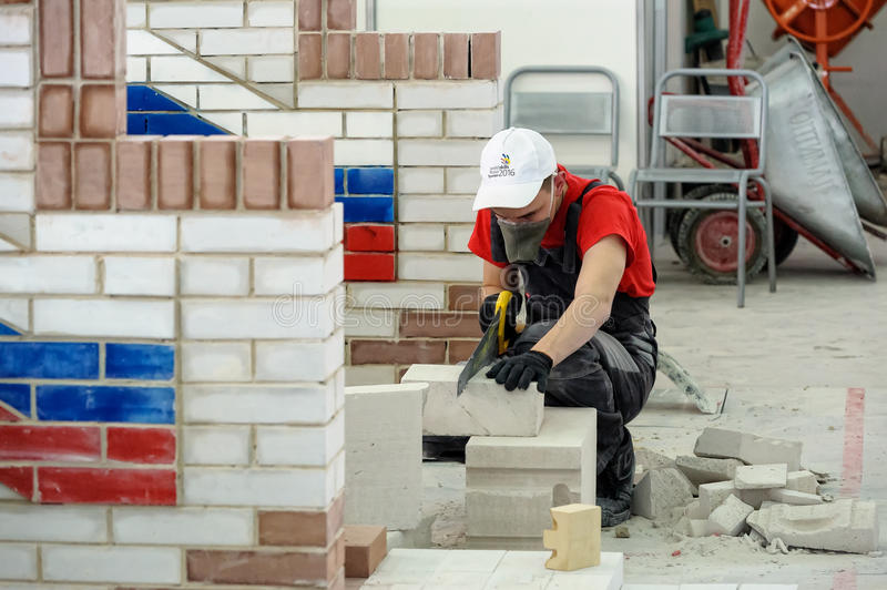 Young bricklayer performs a task of competition. Tyumen, Russia - February 16. 2017: Open championship of professional skill among youth World skills Russia stock photo