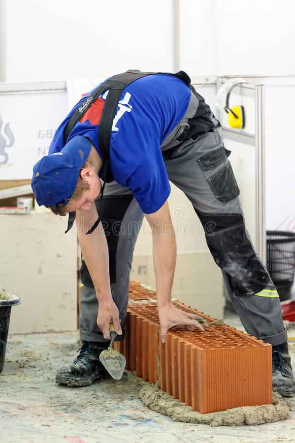 Young bricklayer performs a task of competition. Tyumen, Russia - February 16. 2017: Open championship of professional skill among youth World skills Russia stock image
