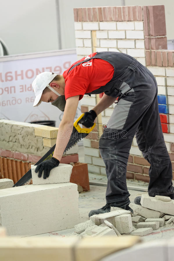 Young bricklayer performs a task of competition. Tyumen, Russia - February 17. 2017: Open championship of professional skill among youth World skills Russia stock image