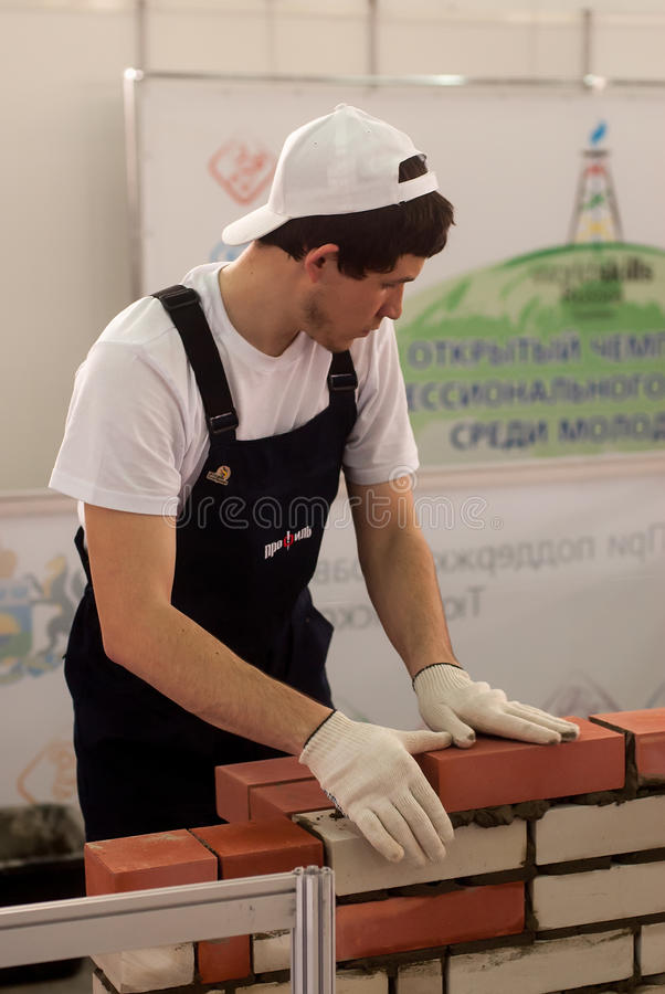 Young bricklayer performs a task of competition. Tyumen, Russia - March 24, 2016: Open championship of professional skill among youth. World skills Russia Tyumen stock photo