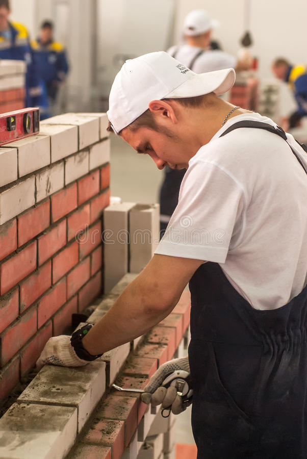 Young bricklayer performs a task of competition. Tyumen, Russia - March 24, 2016: Open championship of professional skill among youth. World skills Russia Tyumen royalty free stock photography
