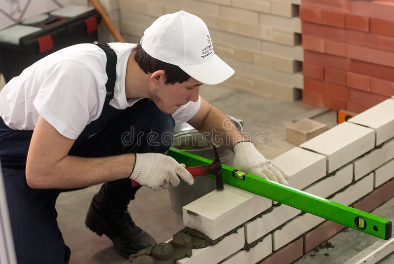 Young bricklayer performs a task of competition. Tyumen, Russia - March 23. 2016: Open championship of professional skill among youth. World skills Russia Tyumen royalty free stock images