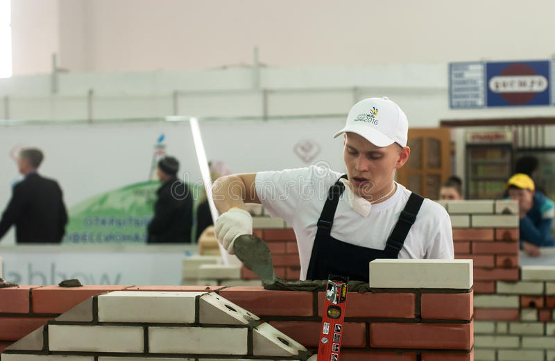 Young bricklayer performs a task of competition. Tyumen, Russia - March 24, 2016: Open championship of professional skill among youth. World skills Russia Tyumen royalty free stock images