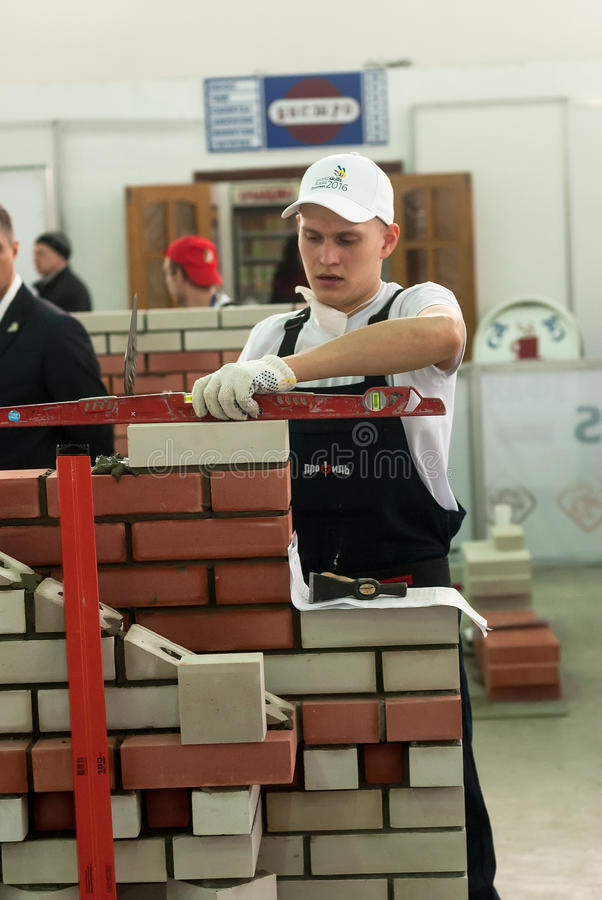 Young bricklayer performs a task of competition. Tyumen, Russia - March 24, 2016: Open championship of professional skill among youth. World skills Russia Tyumen stock photography