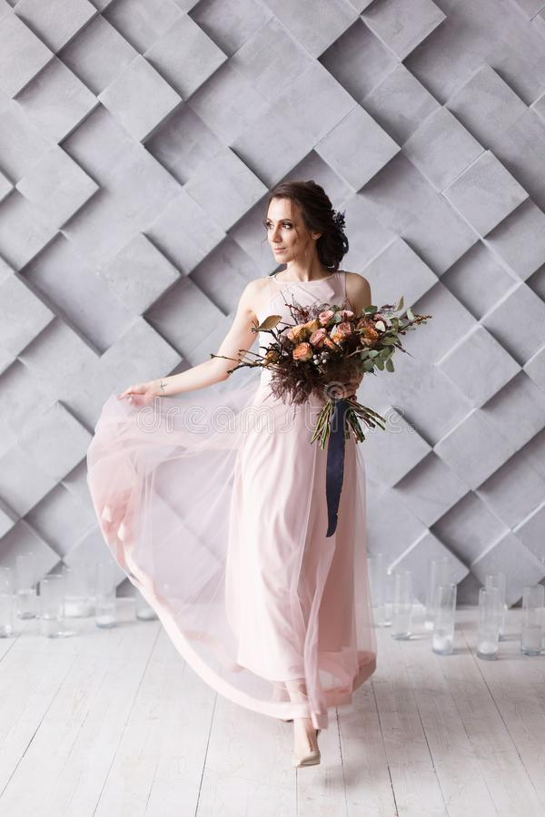 Young bride with coloful bouquet on modern gray geometric background royalty free stock photography