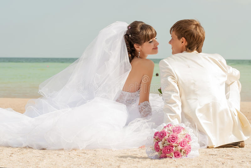 Young bride and groom on the beach stock image