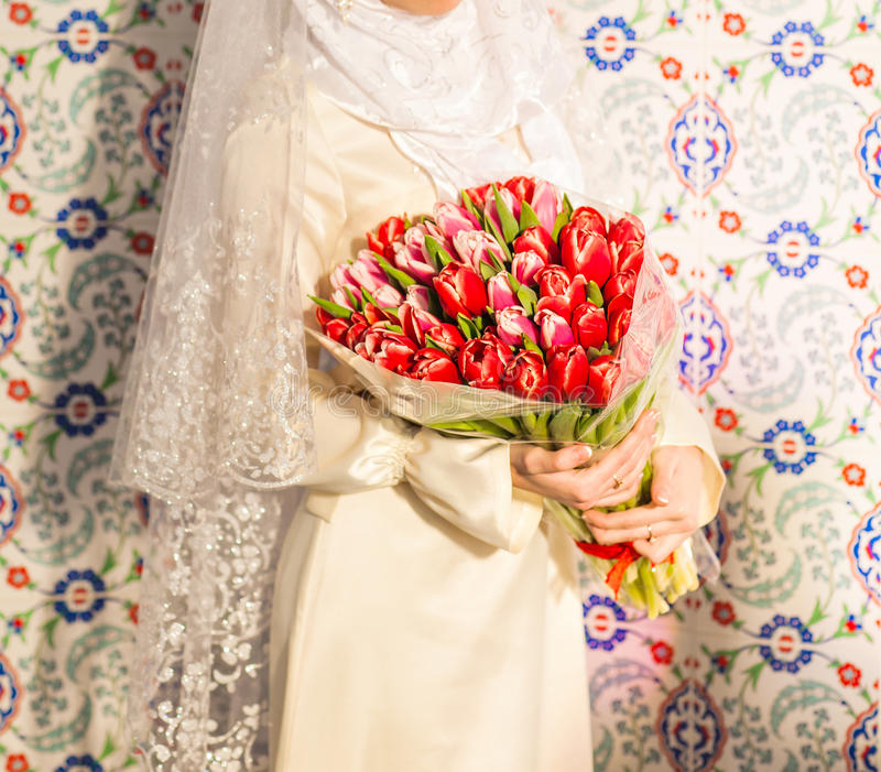 Young bride in islamic clothes posing with flowers indoors royalty free stock photos