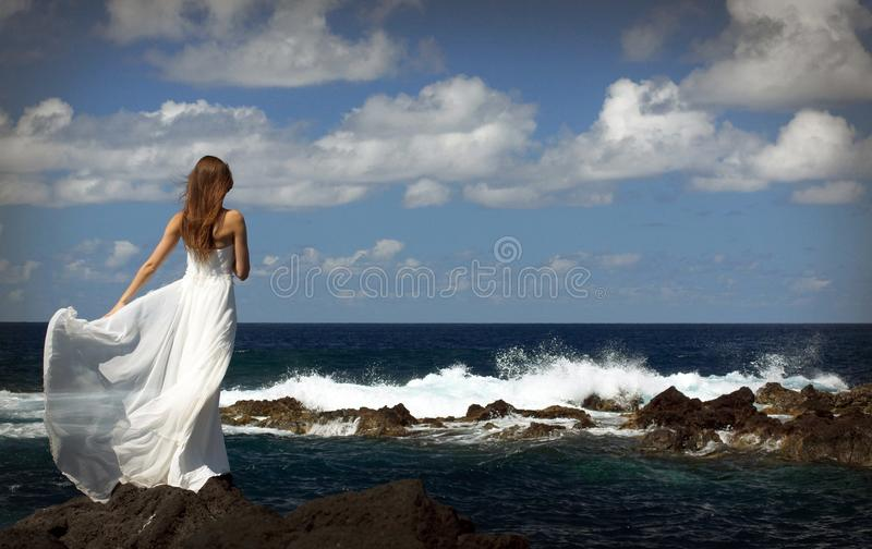 Young fiancee in light white wedding dress standing on windy sea roch shore on Sao Miguel island, Azores. Young bride in light white wedding dress standing on royalty free stock images