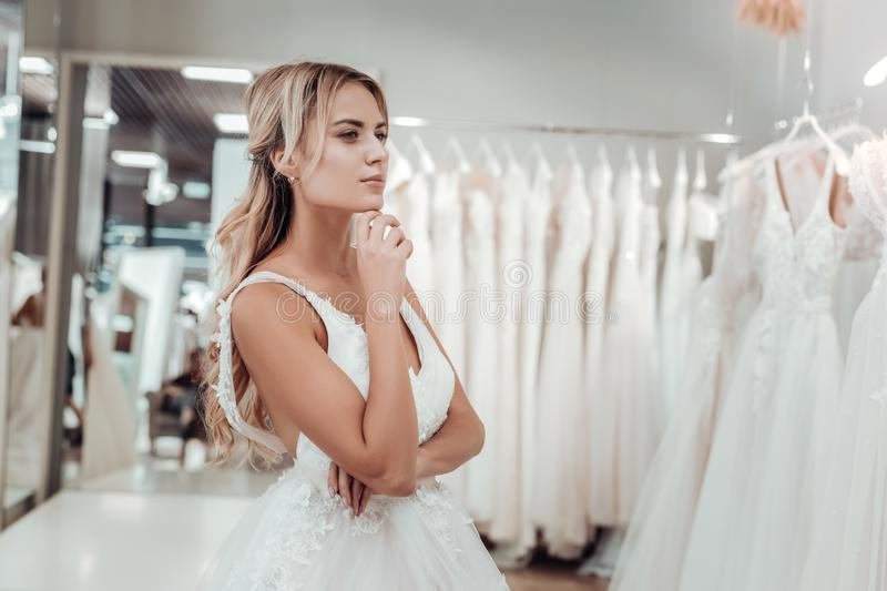 Young bride looking at wedding dresses in a shop. royalty free stock photography
