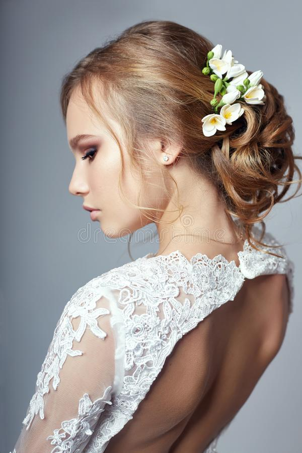 Young bride in a luxurious white wedding dress and beautiful hair. Woman before the wedding ceremony, a perfect figure. Of the bride, beautiful makeup and stock images