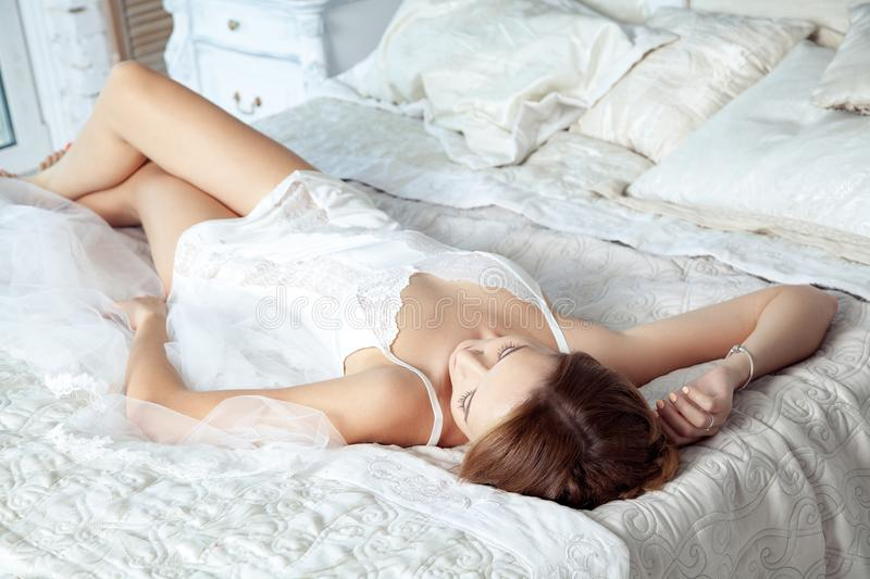 Young bride lying on bed and resting before wedding ceremony stock images