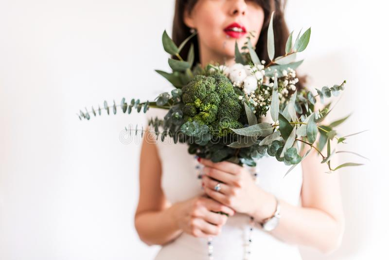 Young bride with modern foodie bouquet. Young bride with red lips and green modern foodie bouquet royalty free stock photography