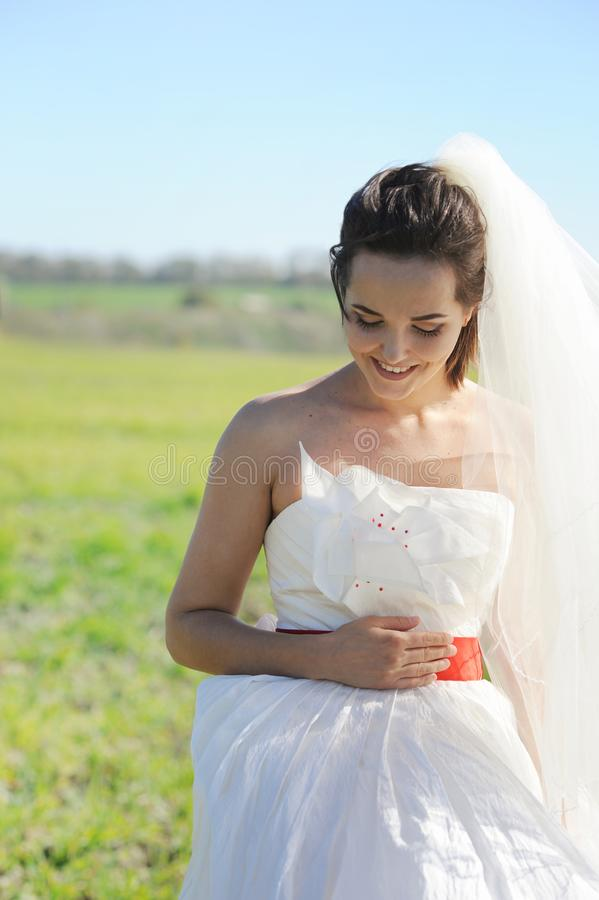 Young bride outdoor portrait in white dress against green field royalty free stock photos