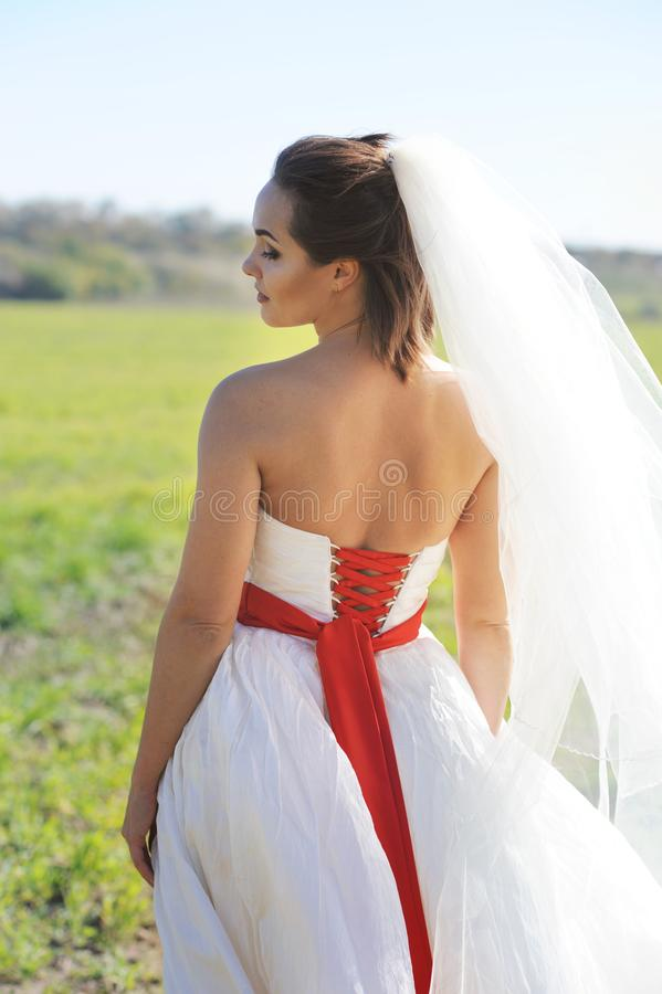 Young bride outdoor portrait in white dress against green field stock images