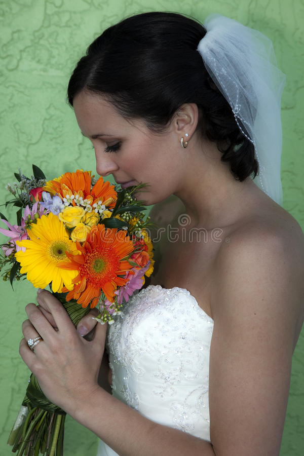 Young bride profile holding flowers royalty free stock photo