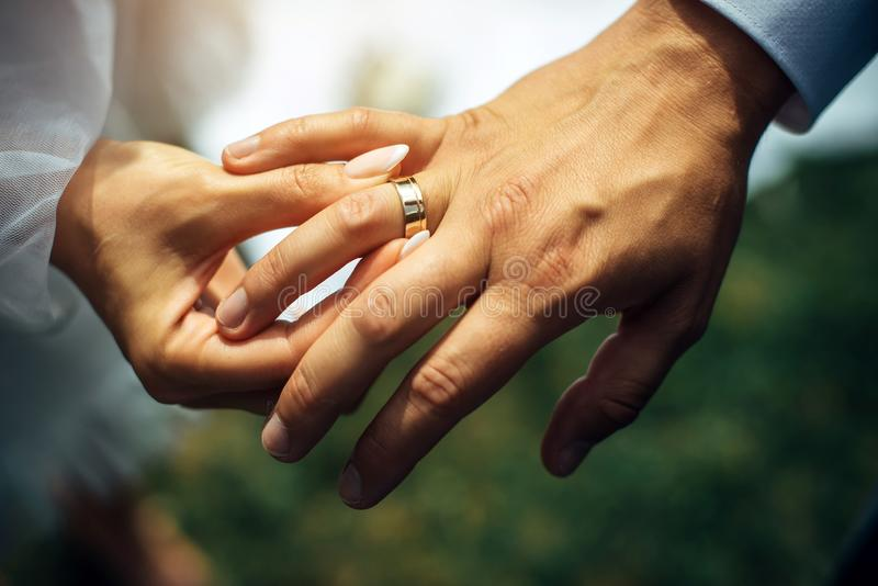 Young bride put a gold wedding ring on the groom`s finger, close-up. Wedding ceremony, exchange of rings. On the hand of man royalty free stock photography