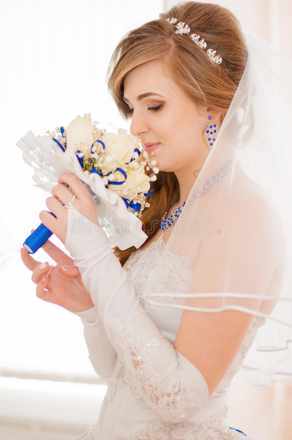 Young bride smelling bouquet royalty free stock images