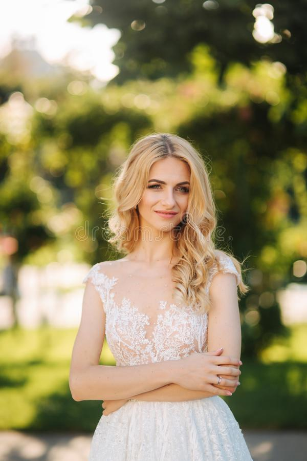 Young bride stand in the park fron of green background.  stock photo