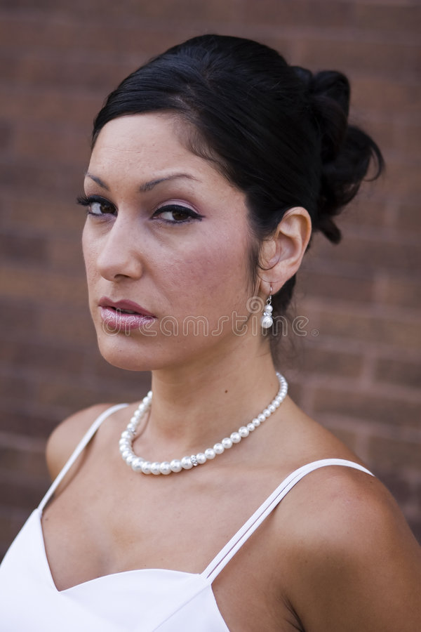 Young bride in wedding dress. Attractive young bride with unhappy expression in white wedding dress stock image