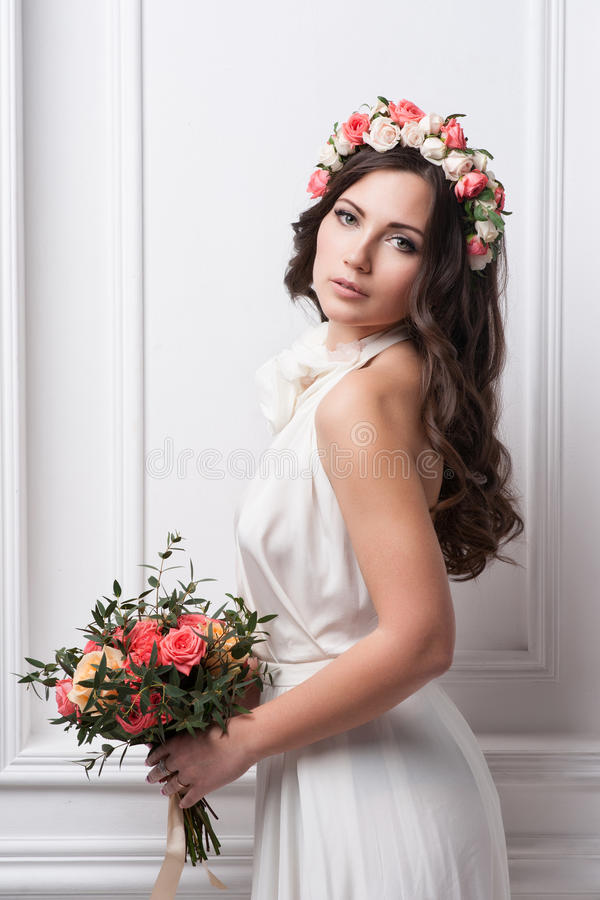 Young bride in wedding dress holding bouquet. Studio shot stock photo