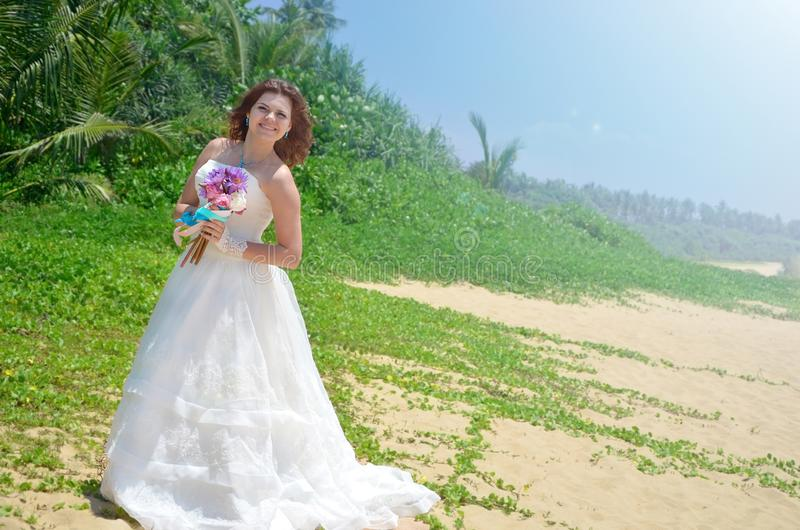 A young bride in a white airy dress is standing with a bouquet of lotuses. girl smiling on a tropical beach on the island. Of Sri Lanka royalty free stock photos