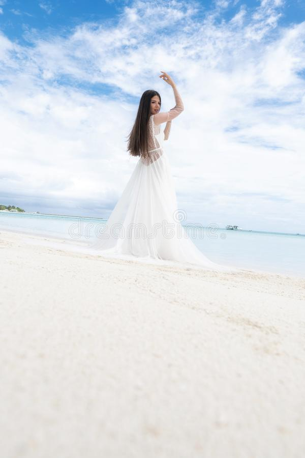 A young bride in a white dress is standing on a snow-white beach royalty free stock images