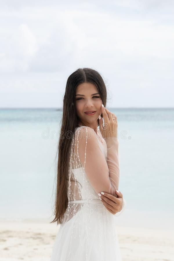 A young bride in a white dress is standing on a snow-white beach royalty free stock photo