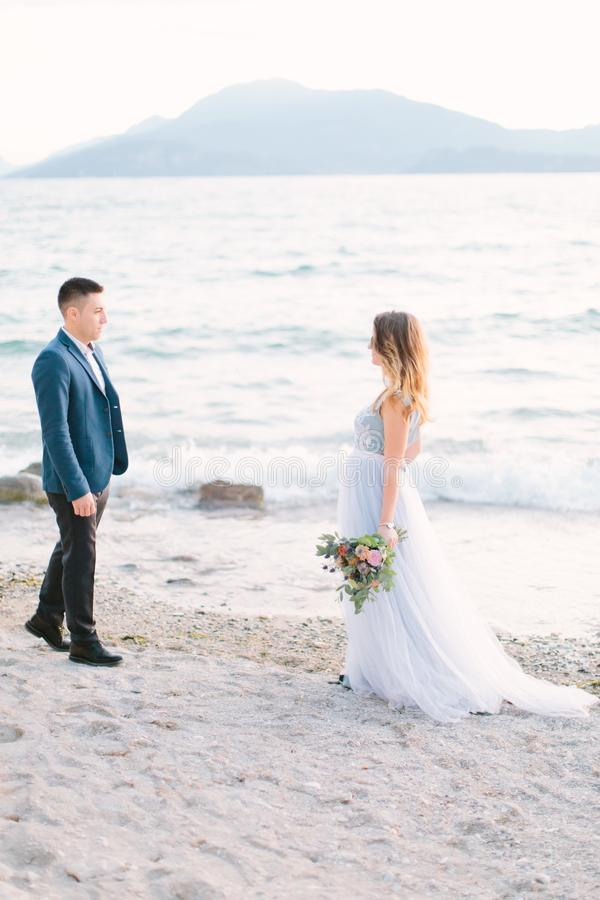 Young bride woman in beautiful blue wedding dress walking to the groom on the beach near the Garda lake. Wedding day and love conc stock photography