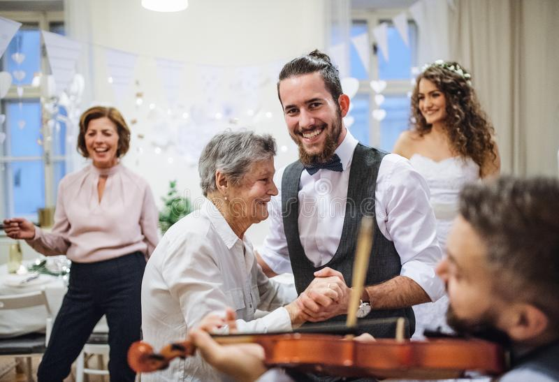 A young groom dancing with grandmother on a wedding reception. stock photos