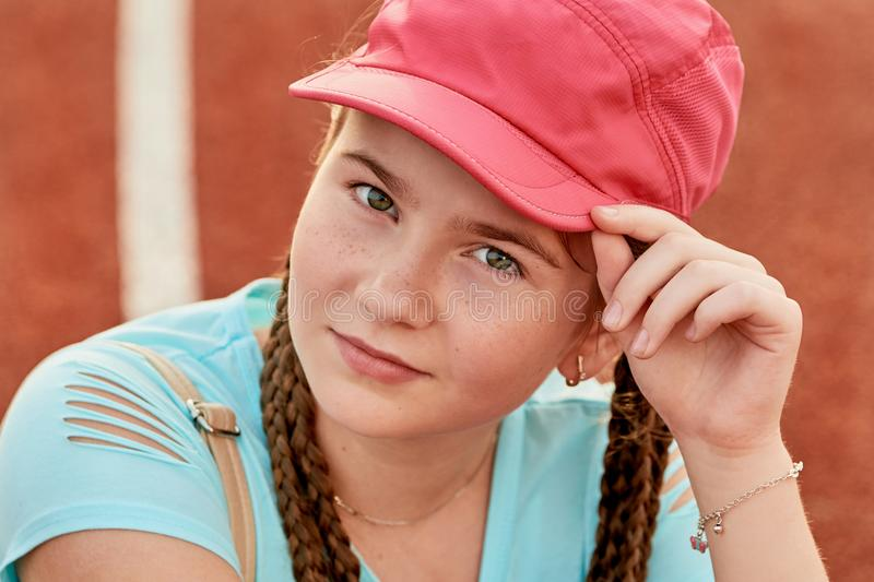 A young bright girl loves sports.sporty girl in a baseball cap. royalty free stock image