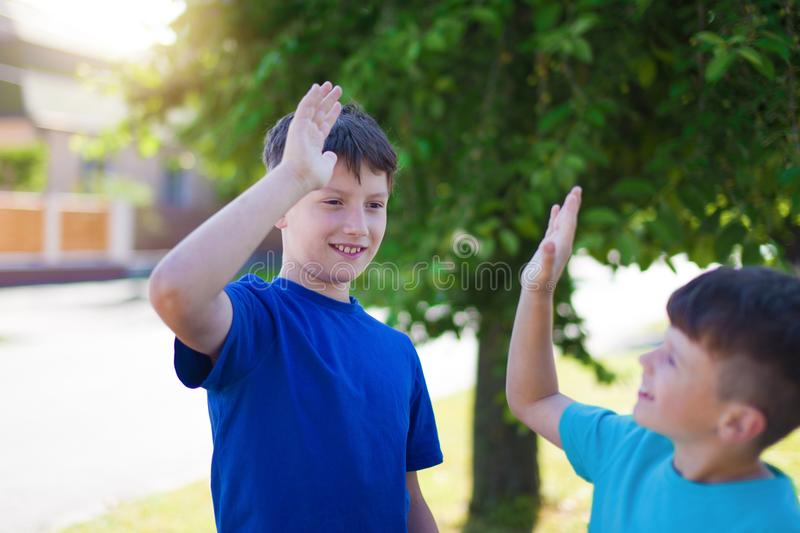 Young brothers high five outdoor. Happy young little brothers high five outdoor royalty free stock photos