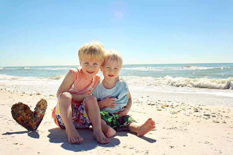 Young Brothers Hugging on Beach by Ocean stock photo