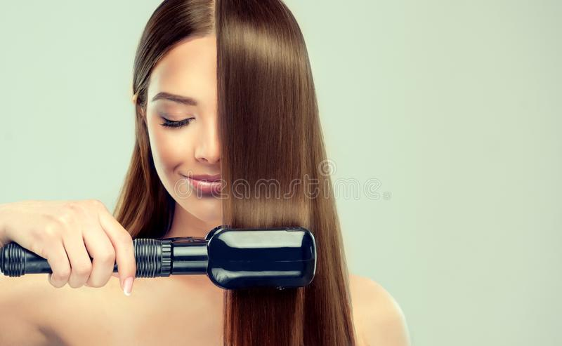 Young woman is demonstrating process of hair straightening. royalty free stock photography
