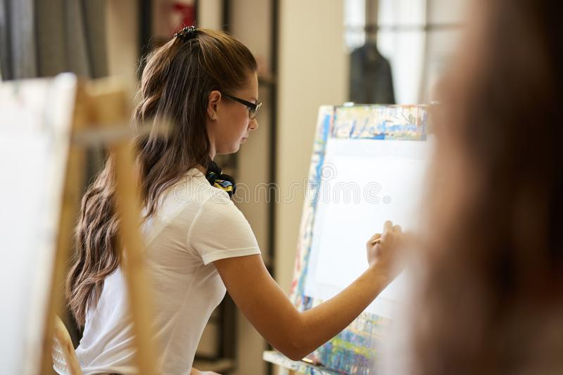 Young brown-haired girl in glasses dressed in white t-shirt and brown apron with a scarf around her neck draws a picture. With a pencil the art studio royalty free stock photos