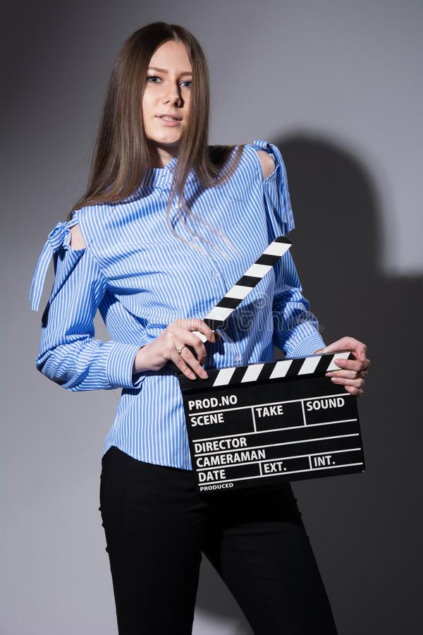 Young brown-haired woman with a movie cracker. Assistant director girl with long hair and striped shirt on a gray background stock photos